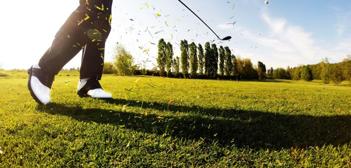 Golfer performs a golf shot from the fairway.